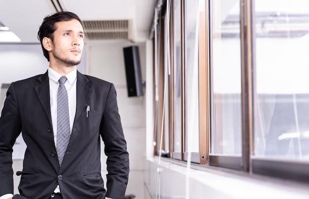 Retrato do homem de negócios considerável que está a janela próxima no escritório.