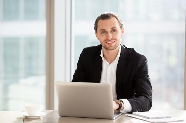 Retrato do homem de negócios de sorriso considerável no trabalho no escritório.
