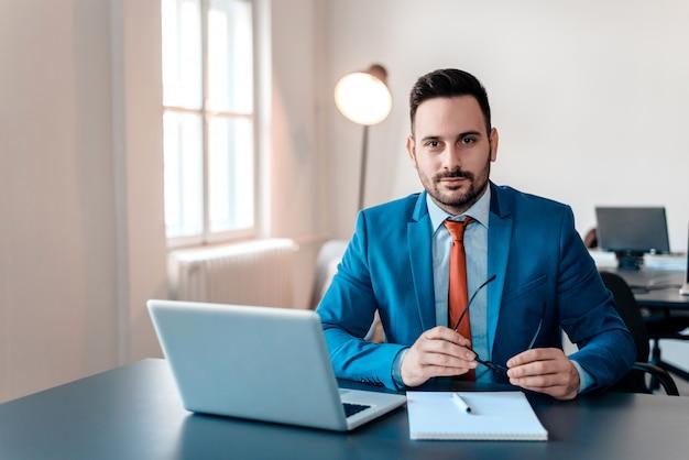 Retrato do homem de negócios de sorriso novo com o portátil que senta-se no escritório moderno.