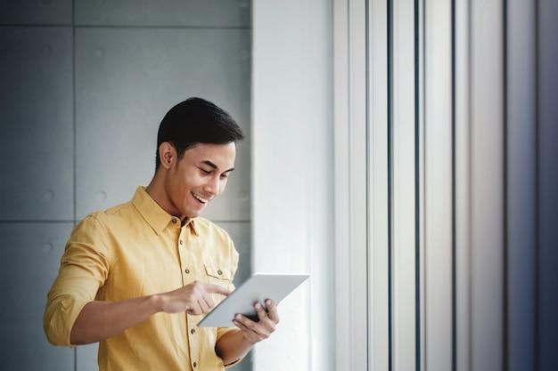Retrato do homem de negócios feliz que está pela janela no escritório.