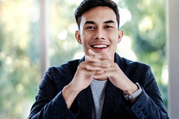 Retrato do homem de negócios novo que senta-se no escritório. olhando para a câmera e sorrindo
