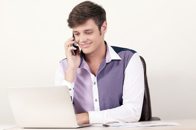 Retrato do homem de negócios novo que usa o telefone celular e o portátil ao sentar-se no escritório e ao trabalhar no relatório financeiro.