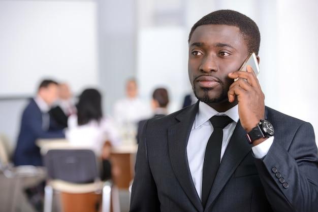 Retrato do homem de negócios preto que que fala no telefone.