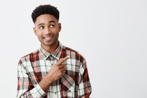 Retrato do homem de pele negra atrativo maduro feliz alegre com penteado afro na camisa quadriculado ocasional que olha de lado com sobrancelhas levantadas e sorriso, apontando com mão na parede branca.