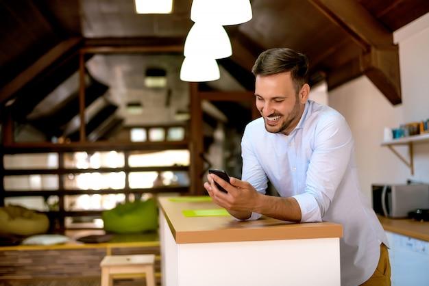 Retrato do homem esperto de sorriso que usa o smartphone em casa.