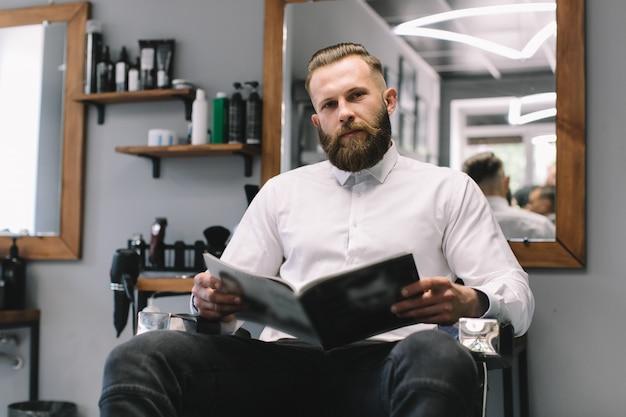 Retrato do homem farpado considerável com penteado elegante e barba na barbearia.