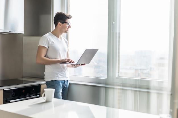 Retrato do homem feliz que guarda o copo e o portátil de café na cozinha em casa. trabalhar em casa em bloqueio de quarentena. auto-isolamento de distanciamento social