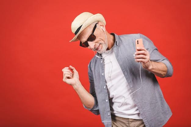 Retrato do homem idoso alegre feliz sênior que dança e que escuta o telefone e os fones de ouvido do witn da música isolados.