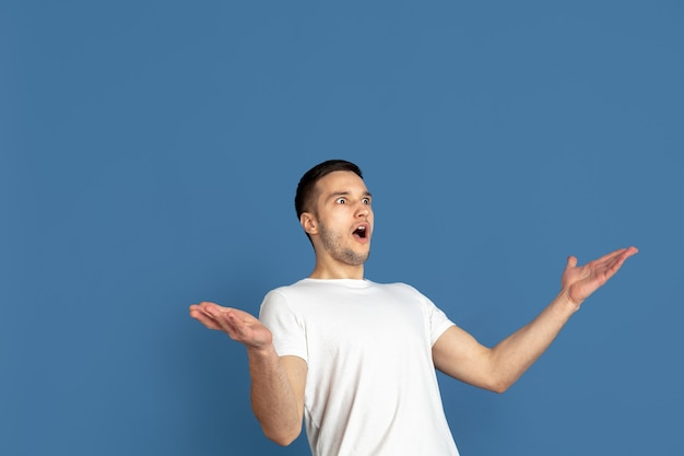 Retrato do homem jovem caucasiano na parede azul