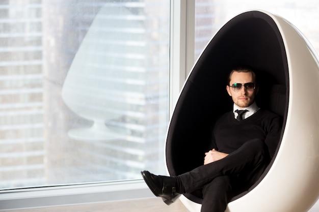 Retrato do homem misterioso à moda na cadeira futurista do ovo.