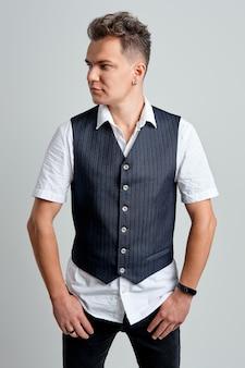 Retrato do homem moderno de camisa branca e colete, olhando para a direita