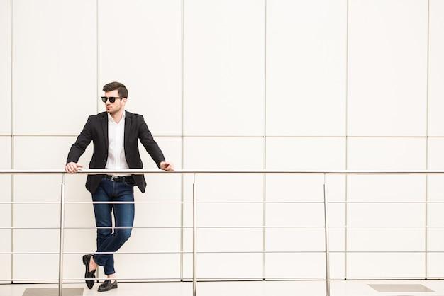 Retrato do homem na moda novo com vidros pretos.