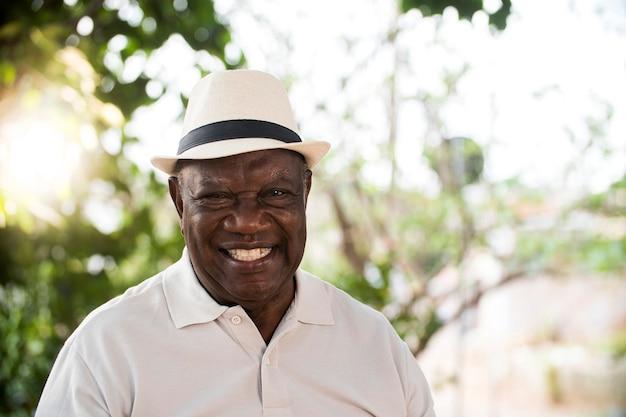 Retrato do homem negro brasileiro sênior com chapéu branco, olhando para a câmera no pôr do sol e sorrindo. forma horizontal, copie o espaço.