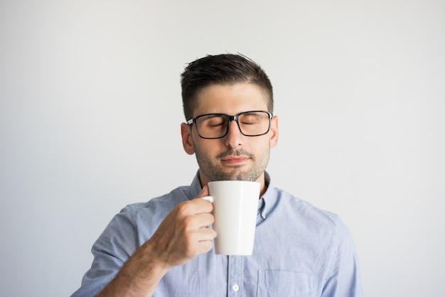 Retrato do homem nos monóculos que aprecia o café com olhos fechados.