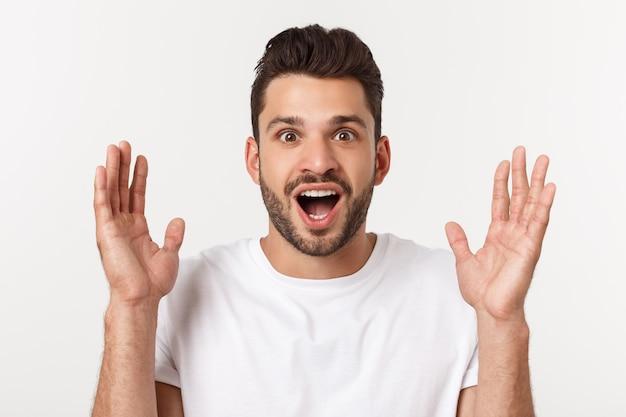 Retrato do homem novo com expressão facial chocada, isolado sobre o branco.
