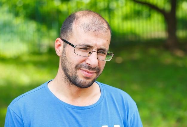 Retrato do homem novo com visão e perda de cabelo ruins.