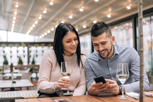 Retrato do homem novo feliz e da mulher que sentam-se junto em um restaurante e que olham um telefone móvel.