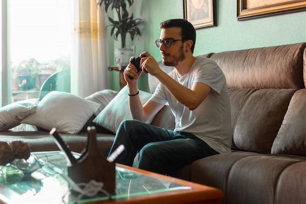 Retrato do homem novo que joga o jogo video que guarda o controlador sem fio em sua casa.