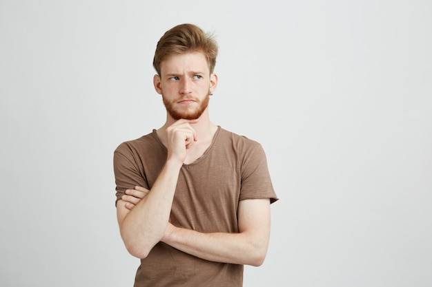 Retrato do homem novo sério que pensa considerando a vista no lado.