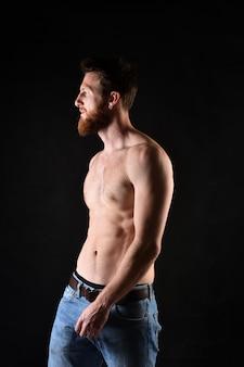Retrato do homem sem camisa e com fundo preto.