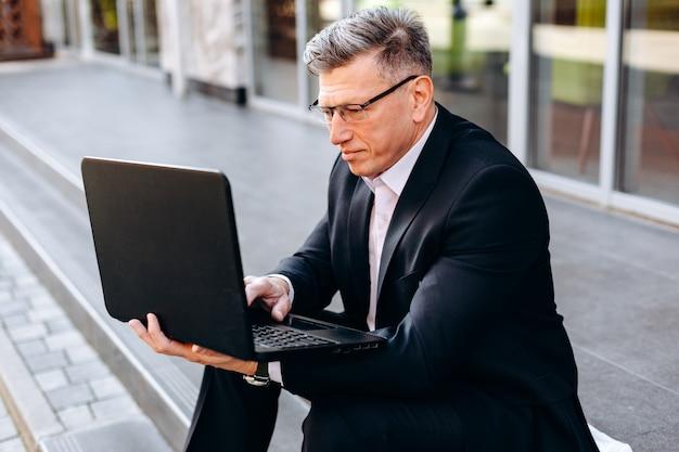 Retrato do homem sênior no terno que senta-se no pavimento e que prende um portátil e que datilografa ao ar livre.