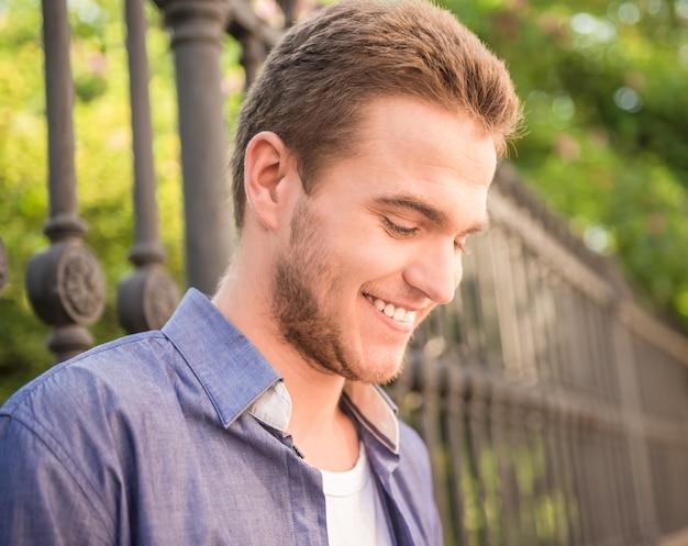Retrato do indivíduo feliz que está perto da cerca no parque.