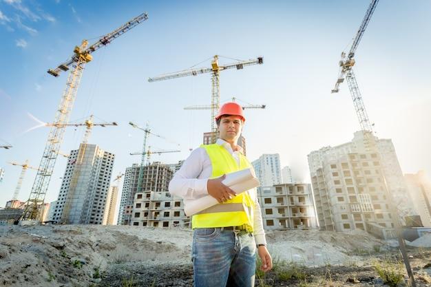 Retrato do inspetor de construção posando com plantas no canteiro de obras
