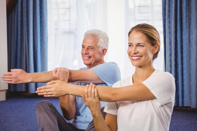 Retrato do instrutor de fitness e senior esticando os braços