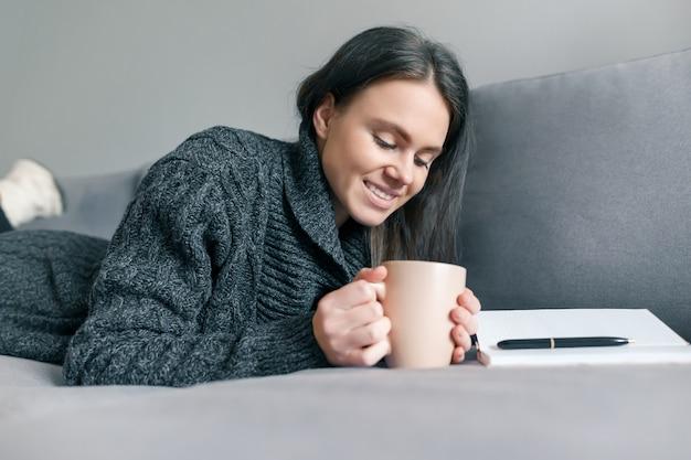 Retrato do inverno do outono da moça na camiseta feita malha morna em casa no sofá com caderno e copo da bebida quente.