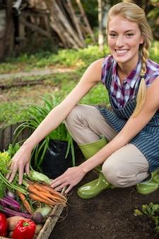 Retrato do jardineiro bonito com legumes frescos no jardim