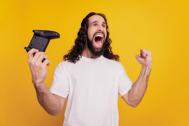 Retrato do jogador vencedor segurando gamepad para jogar videogame em fundo amarelo