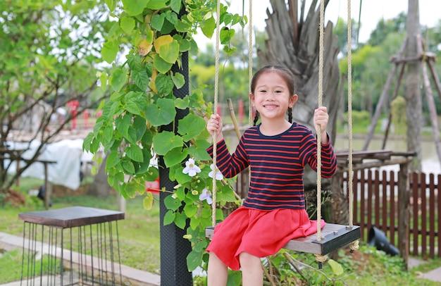 Retrato do jogo asiático pequeno de sorriso da menina da criança e do assento no balanço no parque natural.