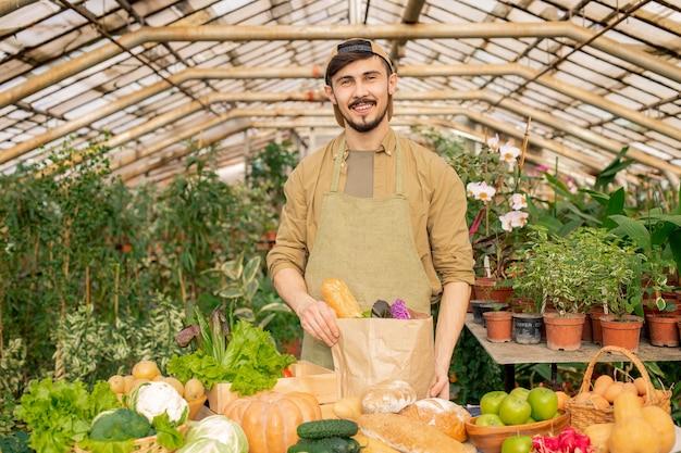 Retrato do jovem agricultor barbudo sorridente de boné e avental em pé no balcão com vários produtos e embalando legumes frescos em um saco de papel