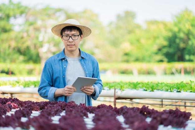 Retrato do jovem agricultor inteligente usando computador tablet digital para inspeção.