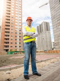 Retrato do jovem arquiteto sorridente em pé no prédio