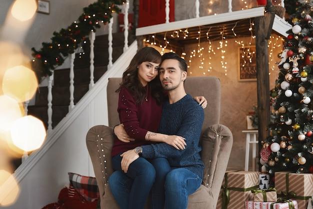 Retrato do jovem casal adorável sentado na poltrona da sala de estar na época do natal