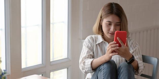Retrato do jovem designer feminino asiático, olhando para o smartphone