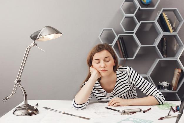 Retrato do jovem designer feminino bonito sonolento, com cabelos escuros na camisa listrada, segurando a cabeça com a mão, adormecendo na mesa durante o trabalho em novo projeto.