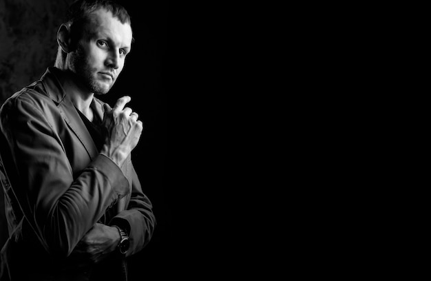 Retrato do jovem diretor de cinema em fundo escuro para kinopremiere. empresário na área de serviços de cinema apresenta o filme. conceito de abordagem séria ao seu trabalho e confiança no resultado. copie o espaço