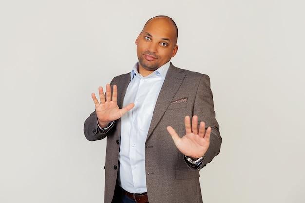 Retrato do jovem empresário afro-americano mostrando as palmas das mãos, demonstrando falta de responsabilidade, levantando as mãos, parecendo perplexo, sentindo-se inocente.