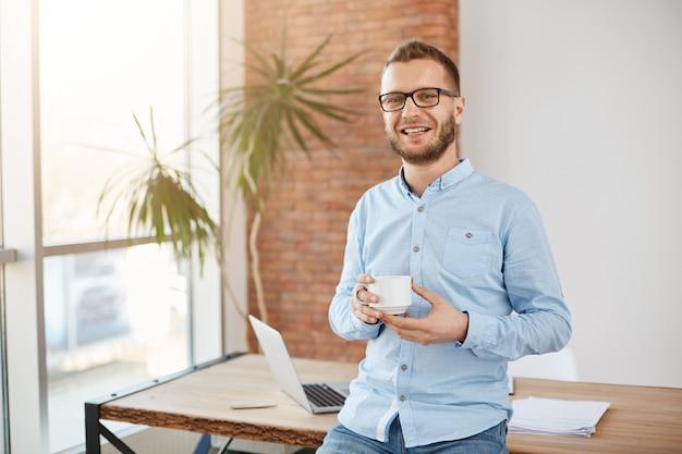 Retrato do jovem empresário barbudo de óculos e roupas casuais, em pé no escritório de coworking brilhante