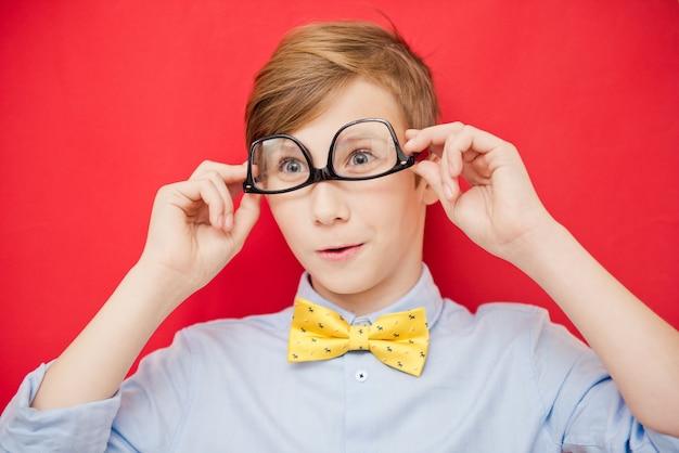 Retrato do jovem empresário de menino em uma camisa e óculos. adolescente de sucesso em um fundo vermelho