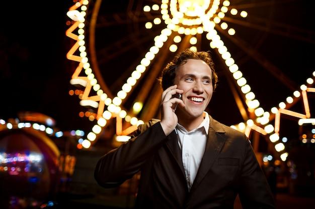 Retrato do jovem empresário de sucesso sobre o parque de diversões à noite. dof raso