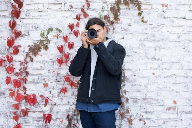 Retrato do jovem fotógrafo iniciante em pé perto da parede branca