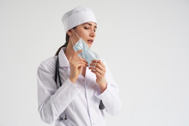 Retrato do jovem médico feminino colocando máscara protetora médica na parede branca, copie o espaço