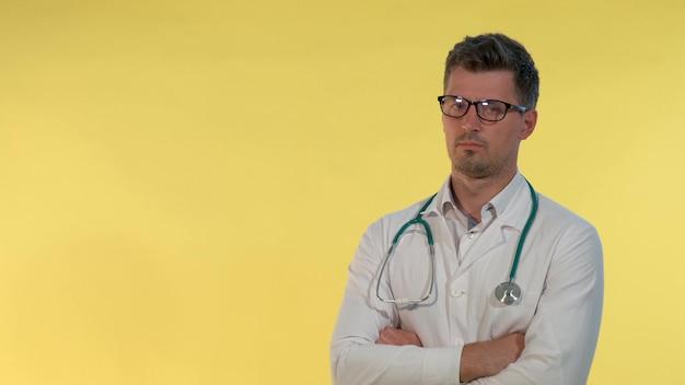 Retrato do jovem médico no jaleco negando algo para a câmera