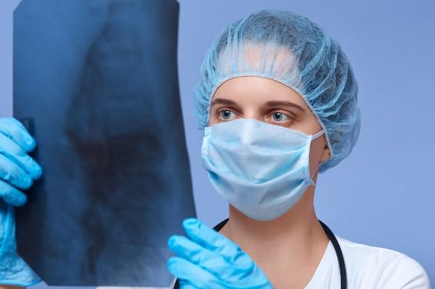 Retrato do jovem médico segurando o raio x roentgen nas mãos e fazendo a análise