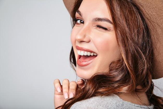 Retrato do jovem modelo rindo elegante em roupas de verão casual cinza com chapéu marrom com maquiagem natural