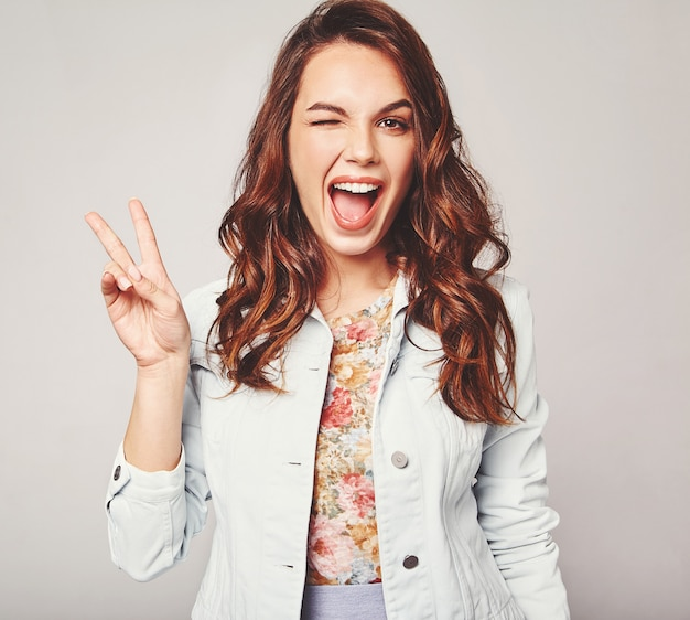 Retrato do jovem modelo rindo elegante em roupas de verão casual colorido com maquiagem natural em cinza