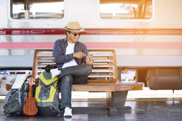 Retrato do jovem turista viajante com mochila sentado esperando a estação de trem e o carro público